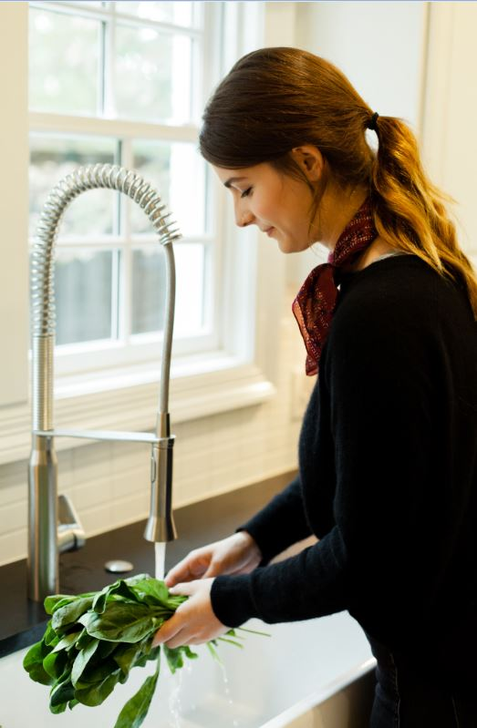 woman washing freshly grown spinach