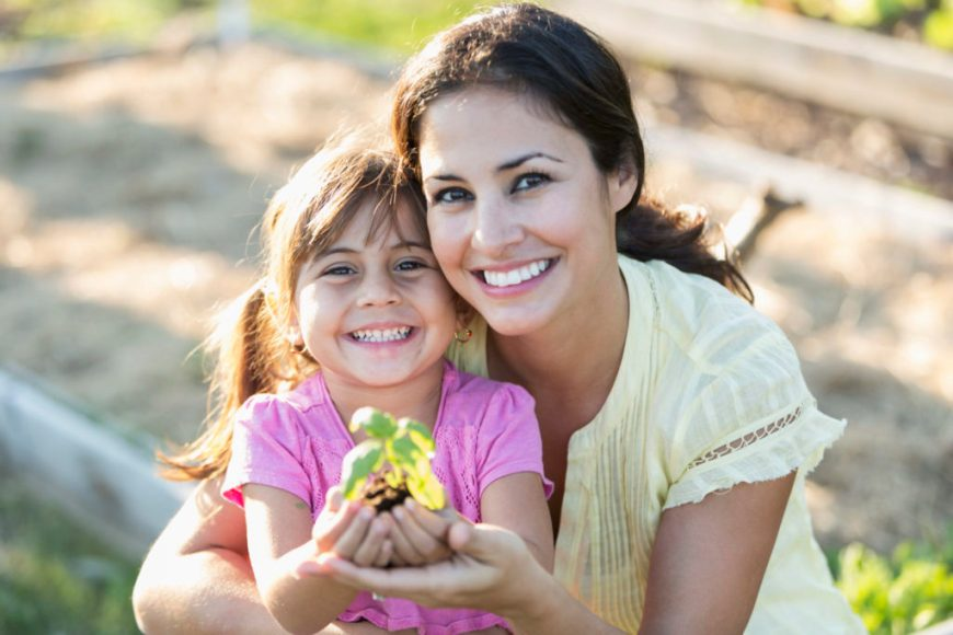 Mother and daughter hold first garden in hand, happily smiling
