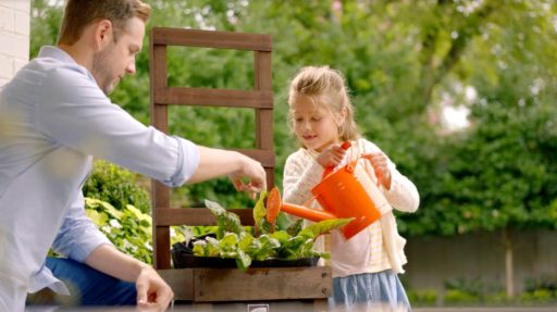 Father & Daughter Watering Their New Housewarming Gift