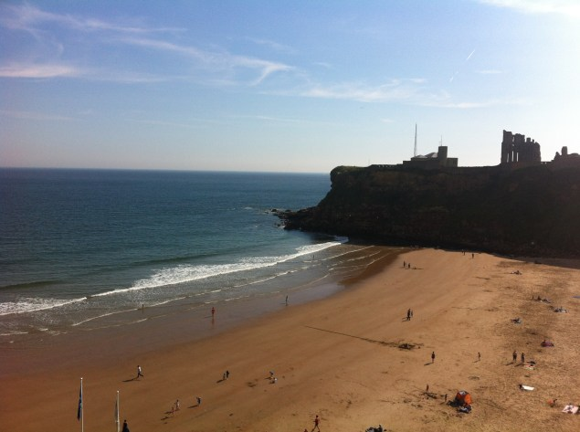Tynemouth Beach - headland with ruins of castle overlooking sandy beach and blue sea