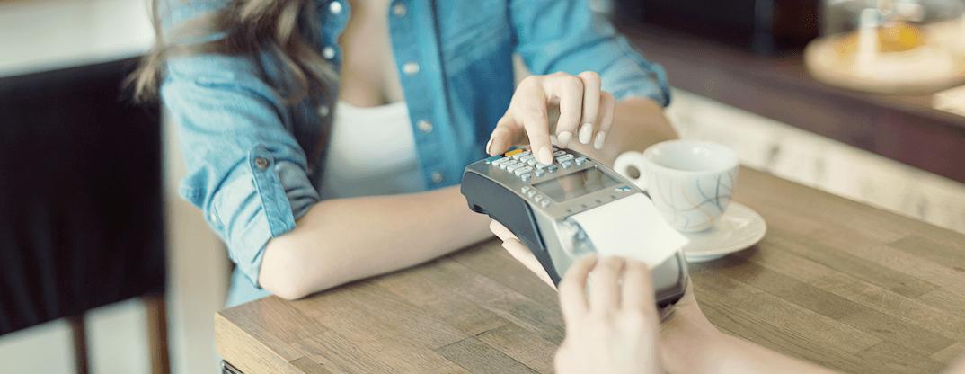 Atendente passando um cartão de crédito na maquininha.