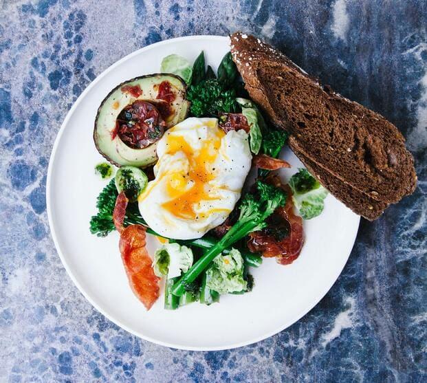 Un plato de aguacate con huevo y una tostada es un ejemplo de desayuno a domicilio en Barcelona