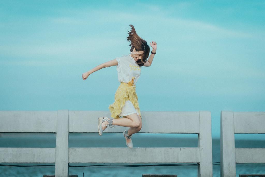 Woman jumping for joy on boardwalk