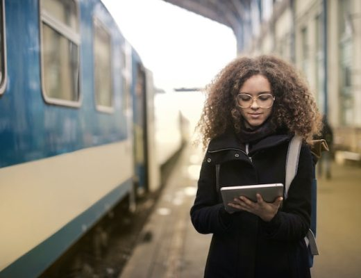 person using tablet on train platform