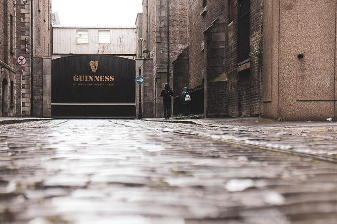 A woman standing outside of the Guinness Storehouse gate in Dublin, Ireland.