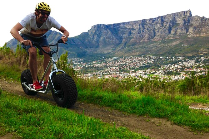 A man riding an off-road scooter down a mountain in Cape Town.