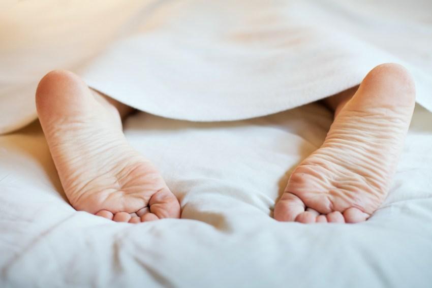 Photo d'une paire de pieds dépassant d'une couverture