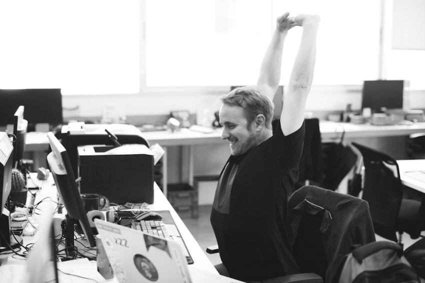 Travailler de chez soi et sédentarité image noir et blanc d'un homme qui s'étire sur son poste de travail