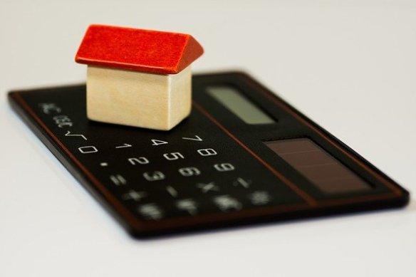 Maqueta de una casa sobre una calculadora. Reflejo de cómo ahorrar en comida