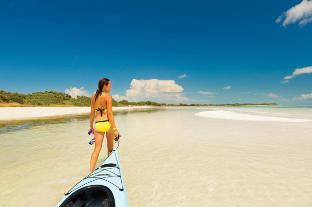 Woman in yellow bathing suit pulls her kayak along the shallows over clear water.