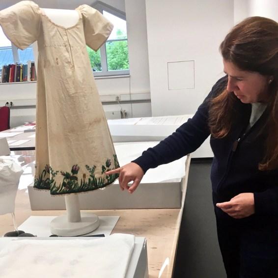 Textilrestauratorin Carola Berriola mit einem Taufkleid, um 1820, Baumwolle, mit Glasperlen bestickt