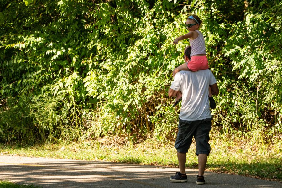 A young girl sits on her father's shoulder as they walk the paved trail at Miami Whitwater Forest.