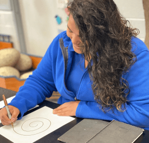 A woman draws a spiral on a piece of paper with a gold marker.