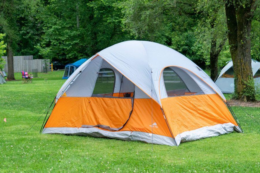 An orange tent sits in a field.