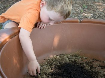 A child digs through the dirt and mud.