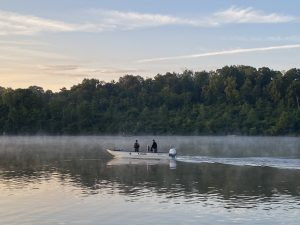 Rangers patrol Winton Lake in their boat at sunrise on Saturday, August 8, 2020.