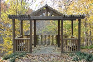 The gazebo at Withrow Nature Preserve overlooks colorful fall foliage on a sunny evening.