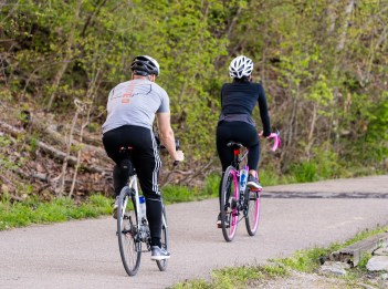 A man and a women ride their bicycles on the Little Miami Scenic Trail.