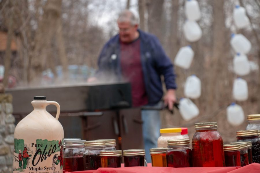 Jars and bottles of maple syrup are lined along a table. Behind them, a man boils maple sap into maple syrup.