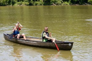 Two children canoe along a lake.