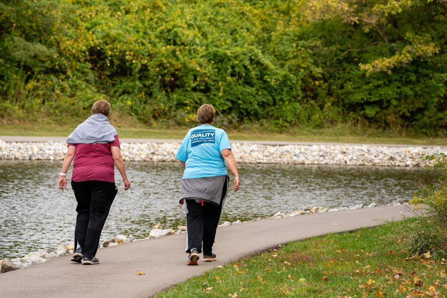 Two individuals walk on a paved path around a pond.