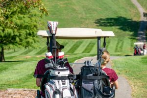 Two people sit in a golf cart, traveling along the golf cart path.