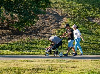 A man and woman walk along a paved trail, pushing a stroller.