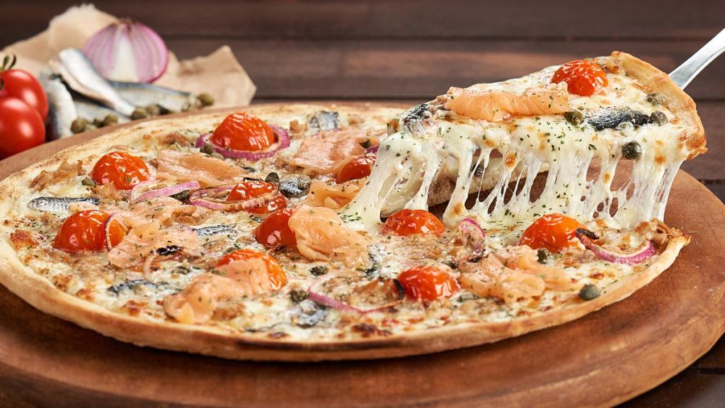 Fotografie culinară cu o felie de pizza Trenta Pescara Artigianale, în timp ce este ridicată de pe blat, cu mozzarella care se întinde.