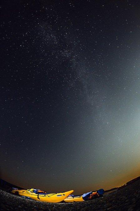 Fotografie cu două caiace la malul Dunării noaptea, cu Calea Lactee vizibilă.