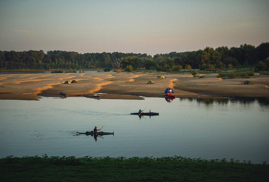 Două caiace pleacă pe Dunăre la răsărit.