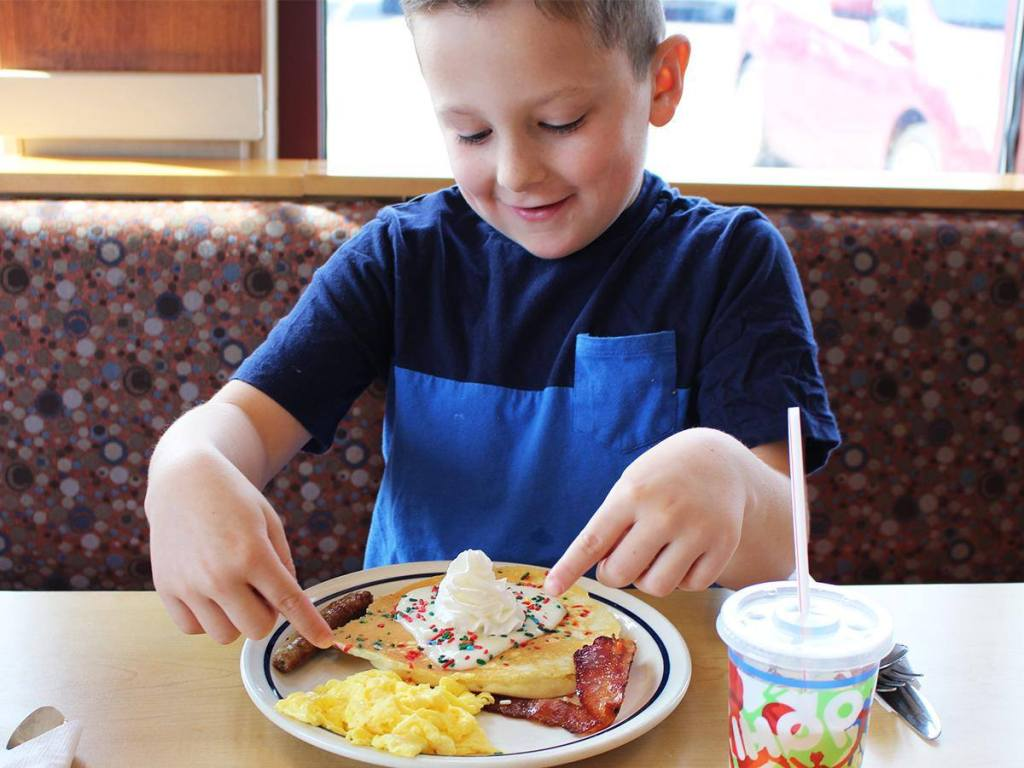 Boy pointing at plate of pancakes and eggs at an IHOP fundraising meal