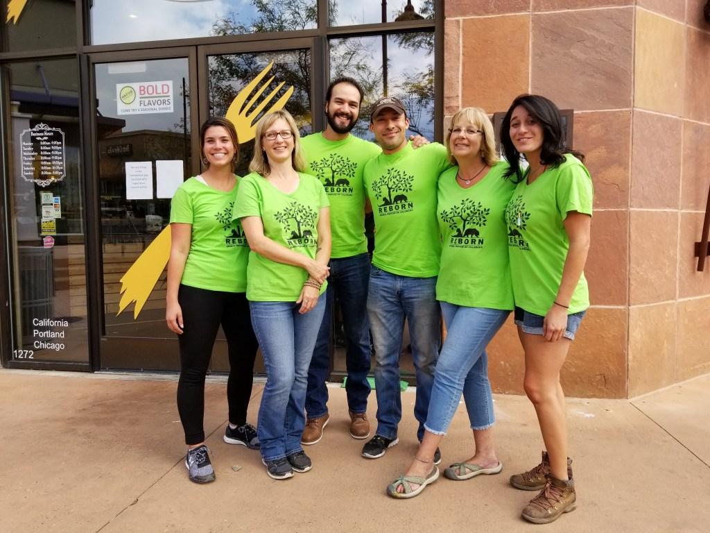 Six people in green t-shirts outside a restaurant.