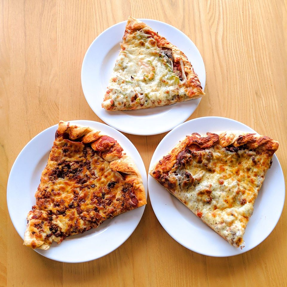 Three slices of pizza on plates at a Jimano's Pizzeria fundraiser
