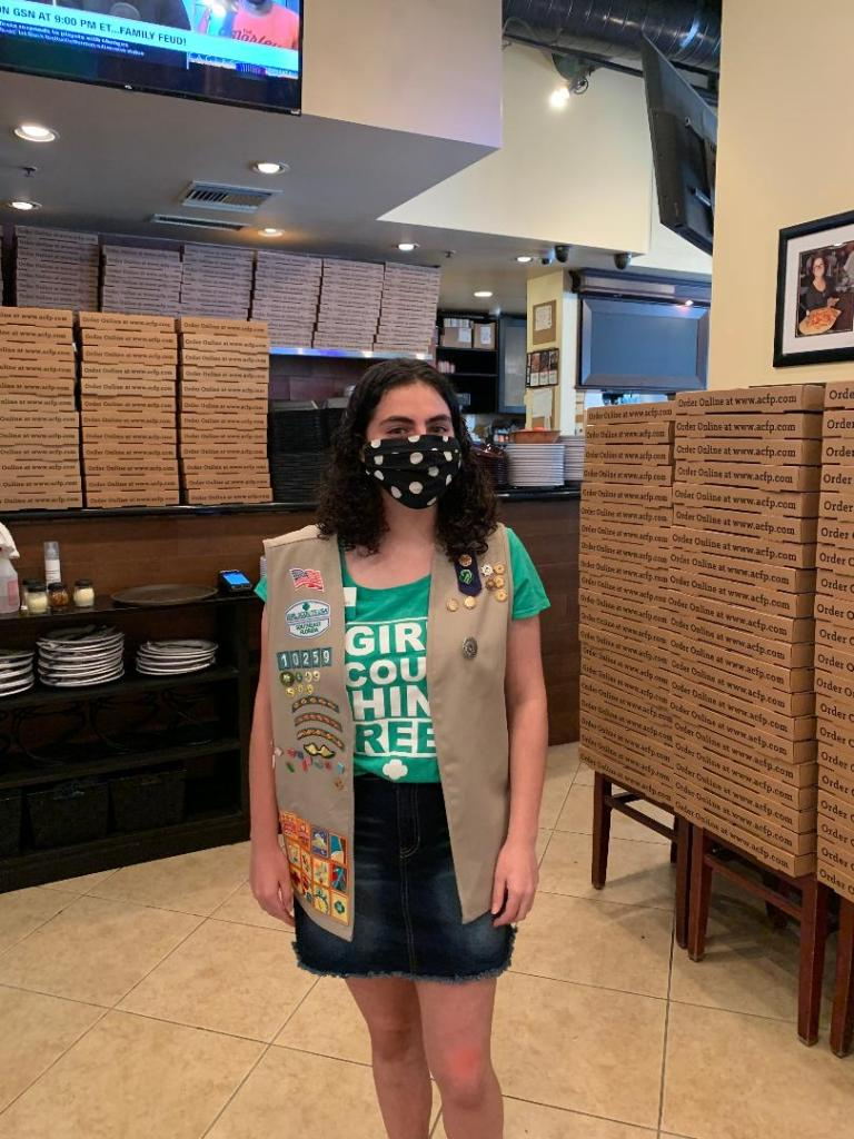 Girl scout wearing a mask in a pizza restaurant