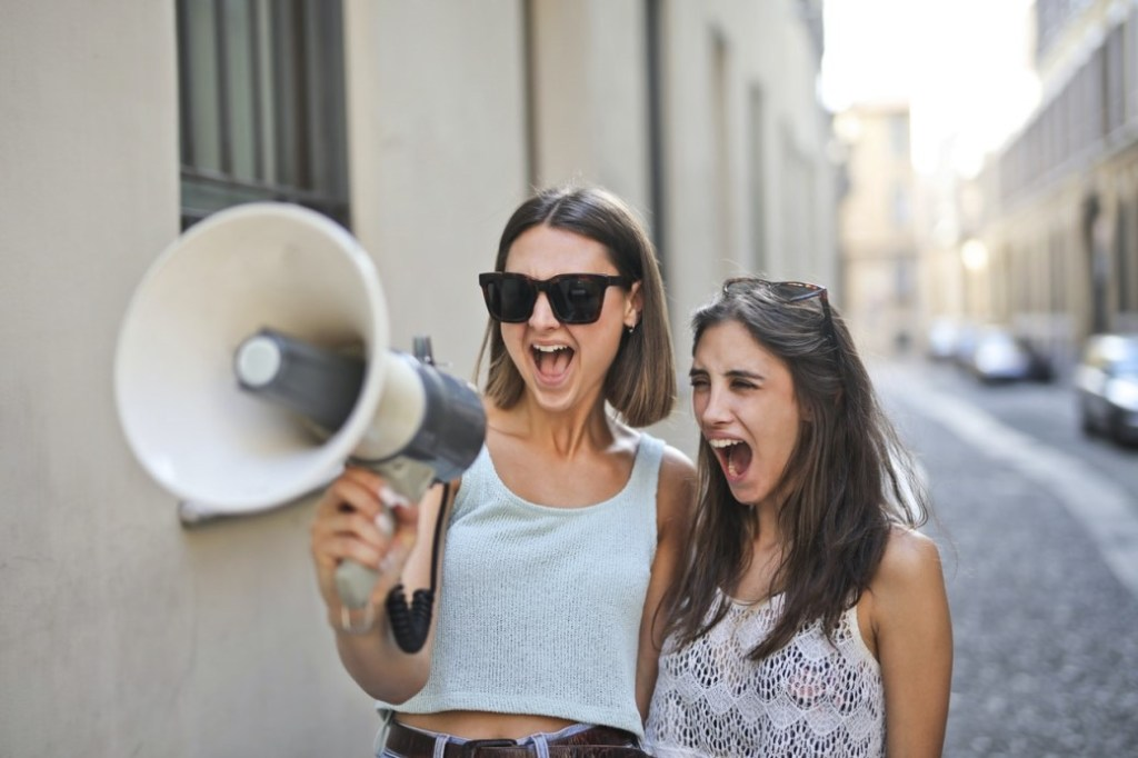 Two women shouting with enthusiasm into a megaphone