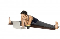 Woman in a yoga stretch position in front of her laptop