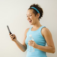 Gym woman smiling at receiving a text message and looking at her phone