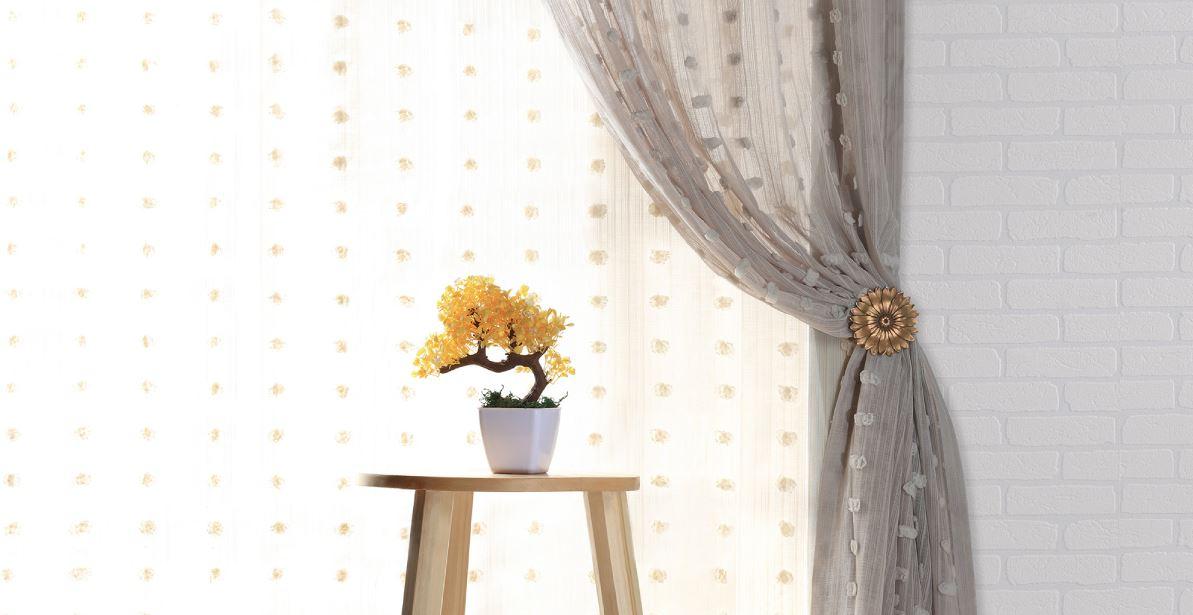 sheer grey curtains behind yellow bonsai tree