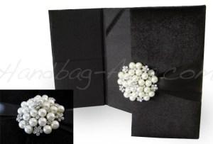 Pearl brooch embellished black velvet invitation folder
