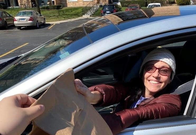 Volunteer handing meal in brown paper bag out of car window