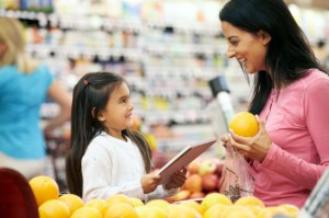 Mother And Daughter At Fruit Counter In Supermarket With List