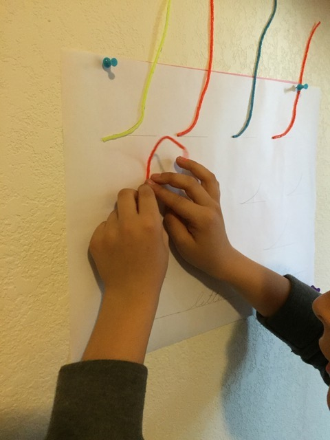Designs With Wikki Stix On A Vertical Surface To Promote Optimal Wrist  Extension.