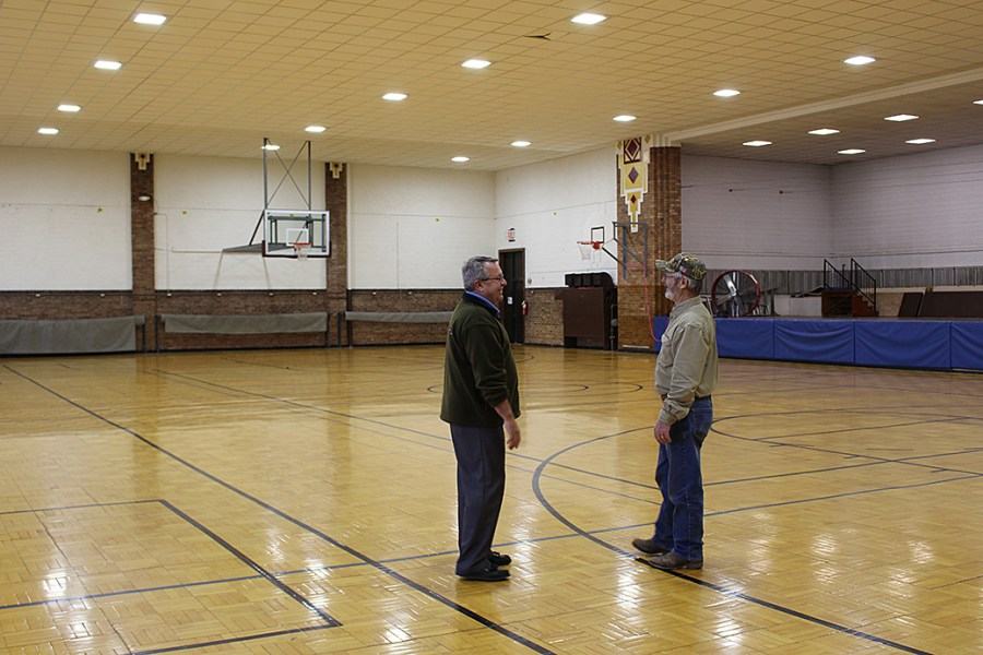 Heartland Customer Relations & Marketing Manager Steve Moses, left, visits with Madison Electric Superintendent Dennis Poppen under the new lights in the Madison Armory.