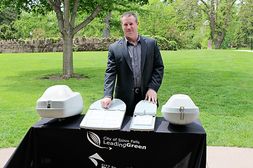 Sioux Falls Light Superintendent Jerry Jongeling stands with new LED streetlighting fixtures (center) which will replace traditional HPS lights (left and right) in the city's pilot project.