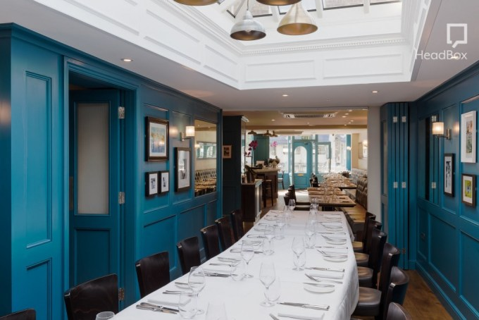 Private dining room at the White Onion Restaurant. Room with ceiling windows, bright blue walls adorned with mounted pictures, a long dining table running the centre of the Space and a view into the main restaurant through an archway at the furthest end of the room.