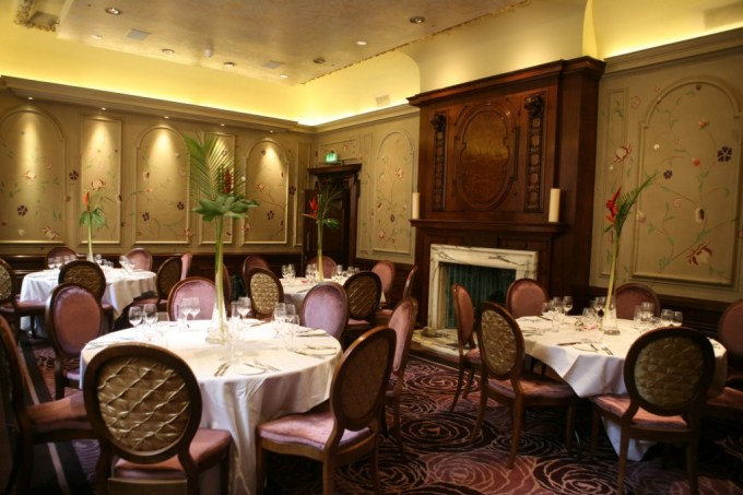 The Eden private dining room at The Forbury: traditionally furnished private dining room with camel coloured walls covered with intricate hand-painted flowers and vines. Four circular tables with white table cloths, tall flower arrangements and musky pink chairs are arranged in front of a large wood and marble fireplace.