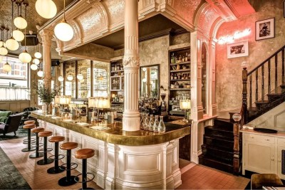 Dirty Bones in Shoreditch is a beautiful Christmas party venue. The curved, white marble bar is the at the centre of this image. With brown leather bar stools surrounding it.