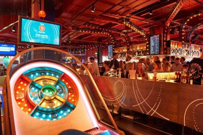 Puttshack is an unusual Christmas party venue in London. You can see their interactive golf course in the forefront of the image which lots of people gathered near the bar in the background.