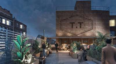 rooftop bar with green plants, wooden floorboards and high brick walls