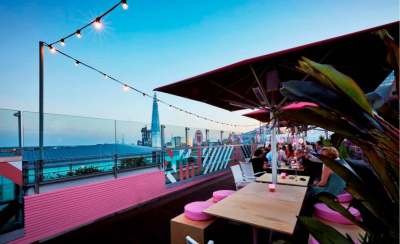 rooftop bar with red canvas coverings, wooden tables and pink seating